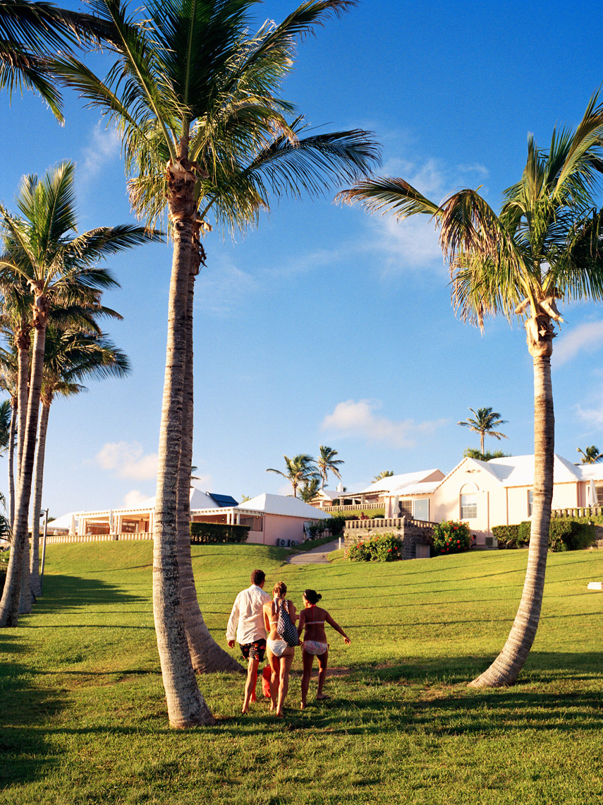 BERMUDA, Cambridge Beach Resort, rear view of family walking towards their bungalow