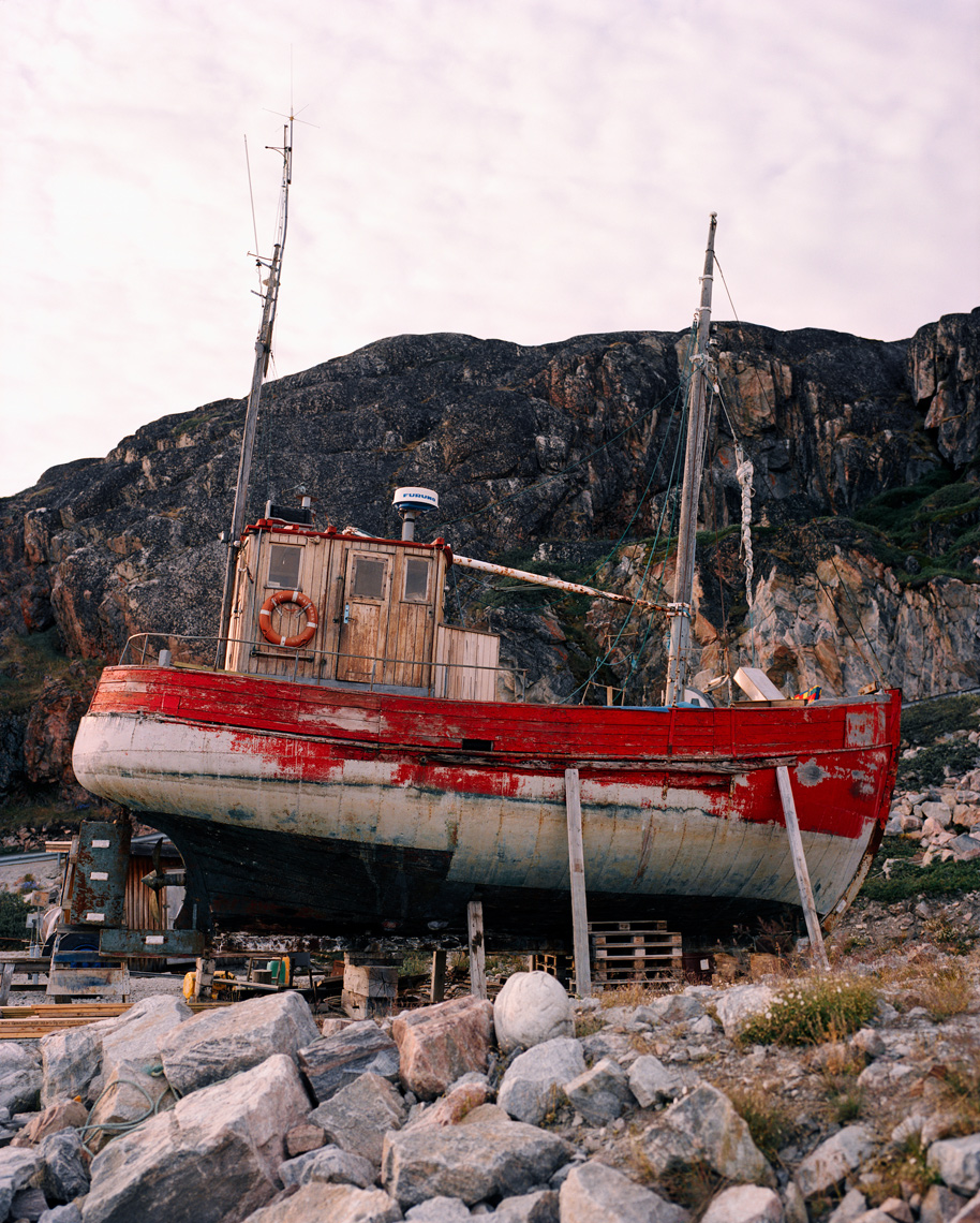 GREENLAND, Ilulissat, Disco Bay, ruined fishing boat in front of rock formation
