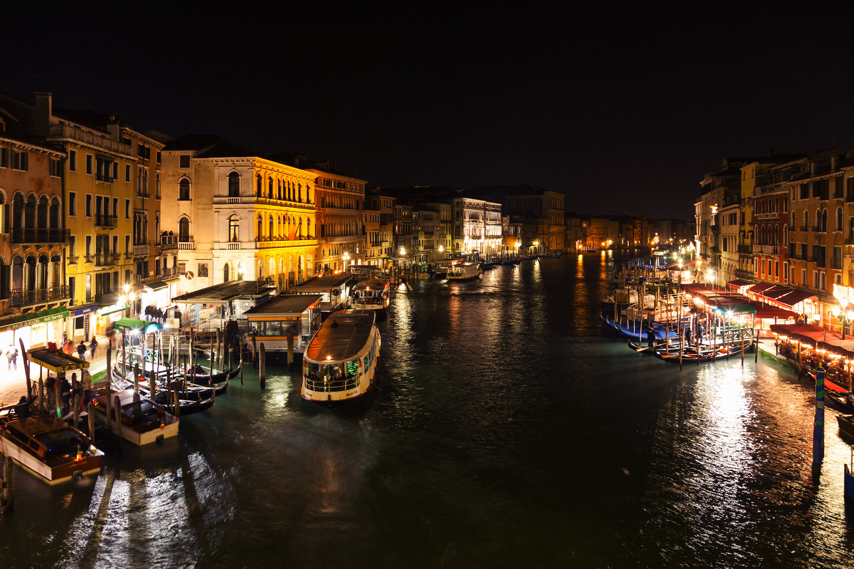 ITALY, Venice. View of the Grand Canal, homes, shops,  and restaurants from the Rialto Bridge at night.