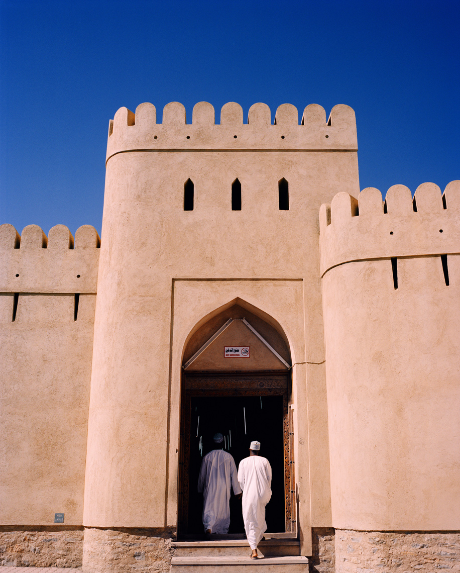 OMAN, Nizwa, men walking on steps to the entrance of a souq.